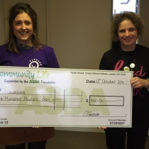 Fundraiser Sophie being presented with a cheque for ASDA